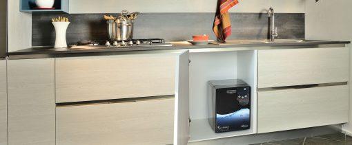 Immagine di un depuratore Produttore d'acqua oligominerale fredda e gassata ambientato in una cucina installato sotto lavello